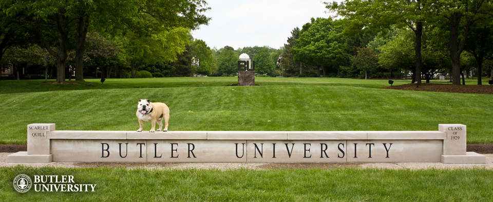 """A bulldog stands on a large stone wall engraved with the words """"Butler University"""". A green field, framed by trees, can be seen in the background."""