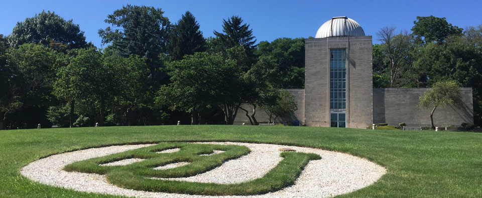 A grass version of the Butler University logo fills the foreground of this photo while the university's observatory can be seen in the background.