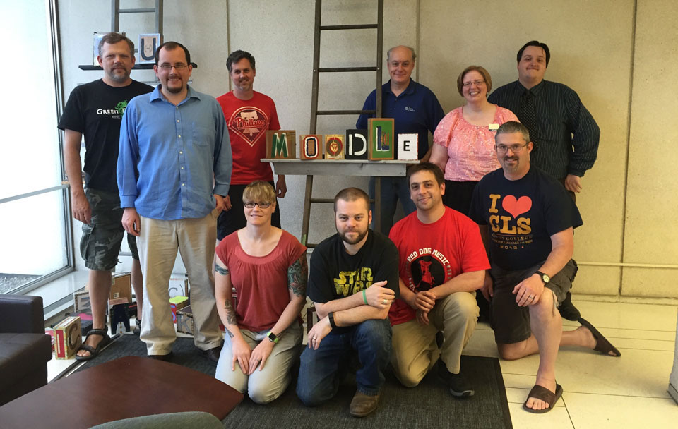 "The ten people who attended Moodle Hack/Doc Fest stand on either side of stylized block letters that spell out the word ""Moodle"".. The"